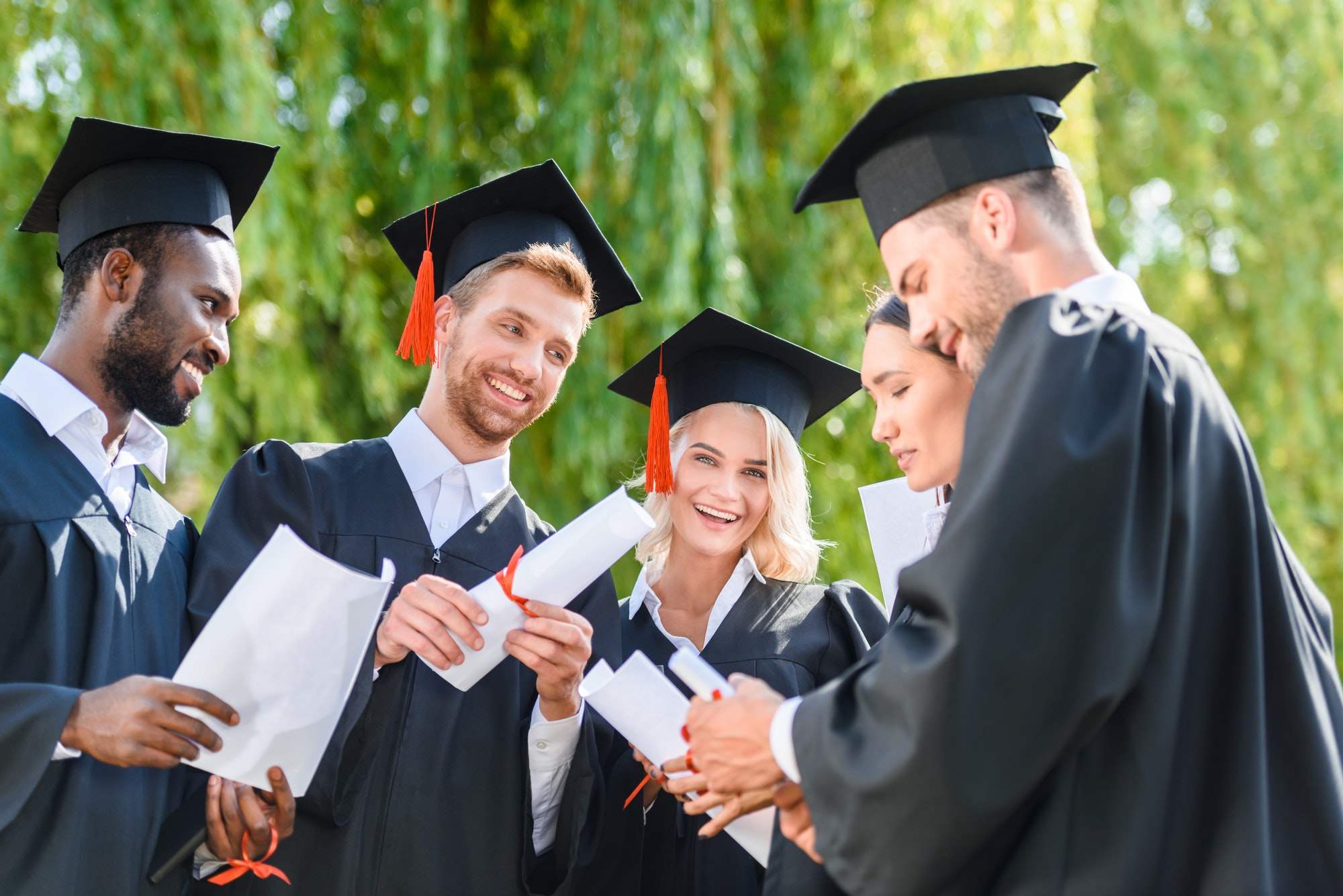 happy young graduated students in capes with diplomas